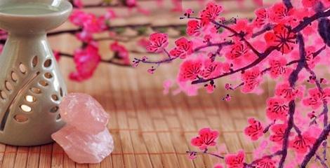 Foto de uma esteira e de um queimador de essencias e um cristal ao lado e de flor de cerejeiras.
