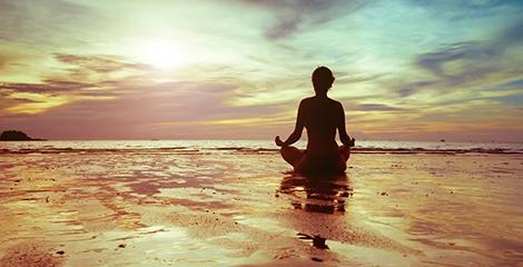 Foto de uma senhora a meditar em frente ao mar calmo e com um ceu ao fundo cor de laranja.